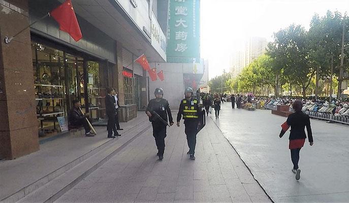 links ein Mann mit Knüppel, mittig zwei bewaffnete Beamte, rechts eine zierliche Figur mit roter Armbinde