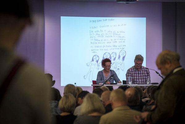 Franziska Röchter und Uwe Hartmann lesen die Texte. Im Hintergrund der Beitrag von Simon Dargel-Agote
