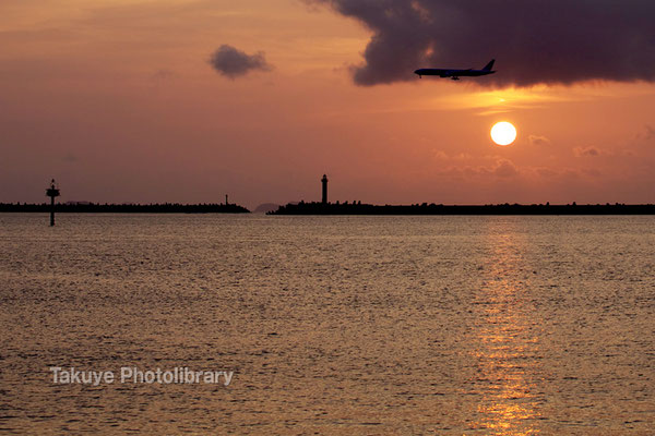 夕陽に染まる那覇港「一文字堤防」の灯台と航空機