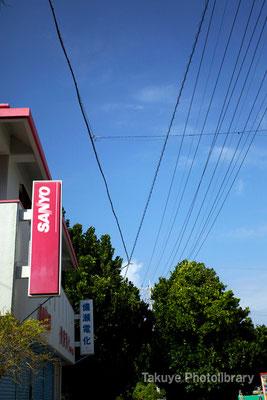 07-0062 備瀬崎部落 まだ残るサンヨーの看板… 空の蒼に赤い看板が映える