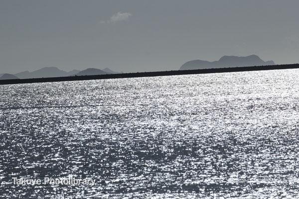 落日前の銀の海。  一直線に伸びる一文字堤防と慶良間諸島