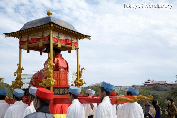 01c-0039 御轎(ウチュウ)に乗る国王。後方に首里城が…