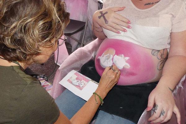 Aan het bellypainten op een baby-shower