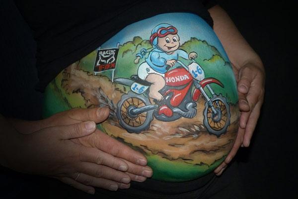 Een stoere buikschildering met baby op crossmotor