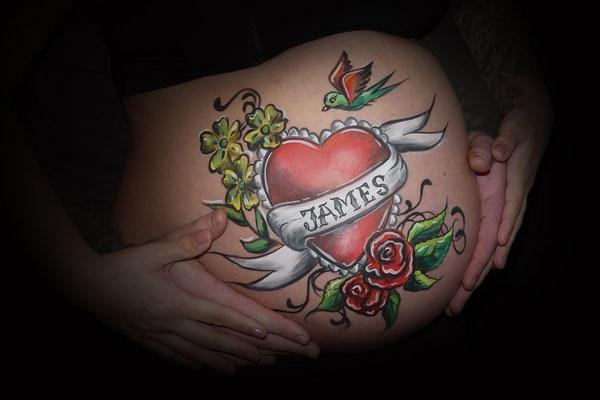 Stoere bellypaint met hartjes en bloemen in tattoo stijl