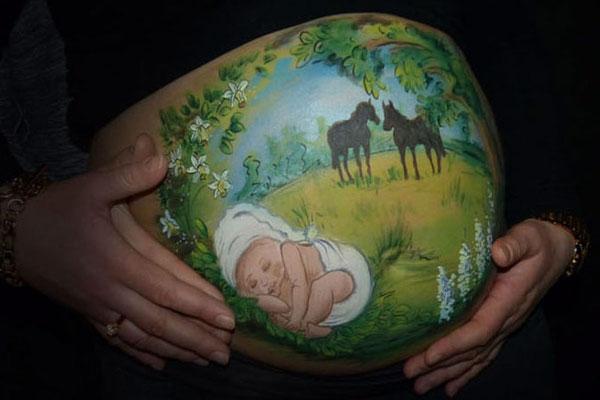 Paardjes op de achtergrond bij deze baby op de beschilderde buik