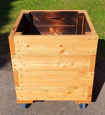 Pflanztrog aus Lärchenholz, geölt, mit Rollfüßen. Maße: L 60 x B 60 x H 60 cm.