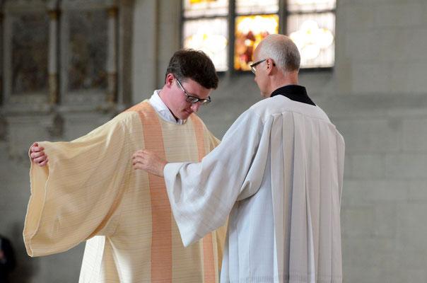 Der Dechant der St. Antoniusgemeinde, Pfarrer Norbert Mertens, kleidet den Diakon in sein neues Gewand.
