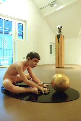 """""""Der Traum des Künstlers"""", 100x60x46cm, Öl, Blattgold auf Wachs, 2000 (Sicherheitsglas), Hintergrund: """"Pechmarie"""",h 35cm, Bitumen, Daunen auf Wachs/Terrakotta, 2009 (Holzsockel)"""