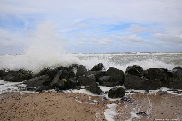 Vorne an der Küste peitscht der Wind die Wellen an den Strand -