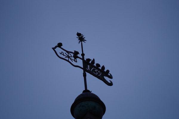 Die Stare sammeln sich zum Flug auf der Kirchturmspitze