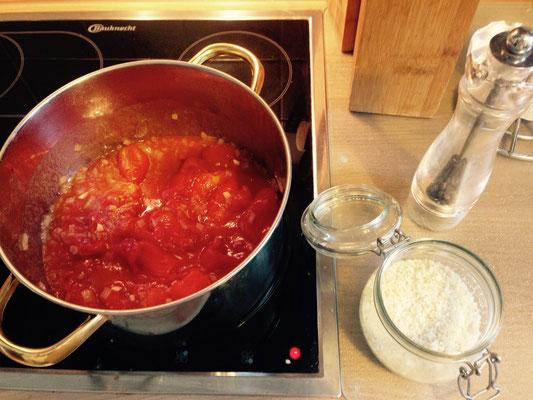 Mit den Tomaten kommt auch der Knoblauch zu den Zwiebeln. Das ganze nun 20-30 Minuten auf niedriger Hitze mit Deckel köcheln lassen.