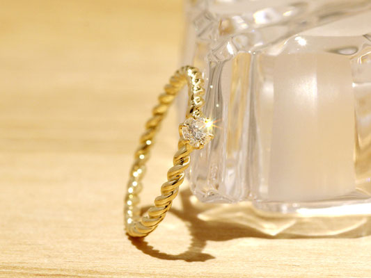 ゴールドの丸線をねじりダイヤモンドを添えた、細身リング。
