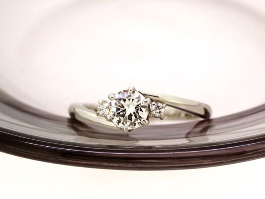 包み込むようなラインを描くアームが優しい雰囲気のダイヤモンドリング。