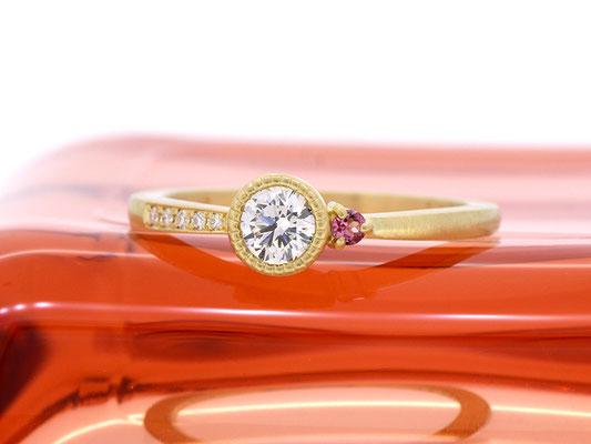 センターダイヤモンドの周りにミルグレインを。ピンクトルマリンがアクセントに
