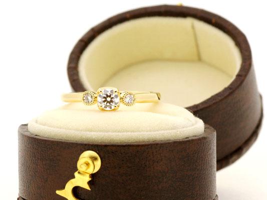 両サイドのメレダイヤモンドはミルグレインで囲みアンティークテイストに