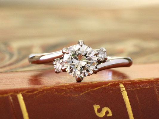 ボリュームのあるセンターダイヤモンドを引き立てる、シンプルなデザインのエンゲージリング