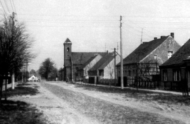 (0387) Dorfstraße, Kirche, 1976 (bei dem Objekt vor der Kirche handelt es sich nicht um das Kriegerdenkmal, das war zu dieser Zeit vergraben)