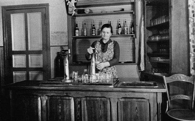 (0485) Emma Ney am Tresen der Gaststätte, im Hintergrund Tür und Durchreiche zum Saal