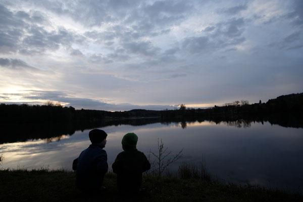 Die Kinder beobachten den Sonnenaufgang am See