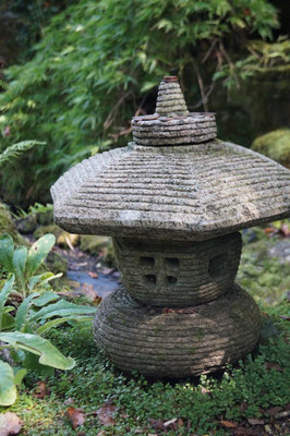 Eine Japanische Laterne mitten in einem schönen Garten. Im Hintergrund fließt ein kleiner, natürlicher Bach.