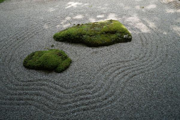Zwei bemooste Steine liegen in einem Kiesbett. Um die Steine sind Ringe gezeichnet, wie auf einem See. Das Weiß der feinen Kieselsteine umrahmt das dunkelgrüne Moos