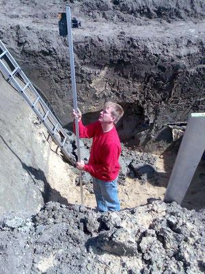 Mit einem Nivelliergerät wird die tiefe der Baugrube ermittelt.
