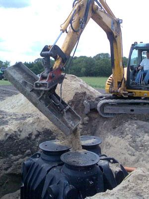 Die Baugrube wird mit Sand und Kieß gefüllt.