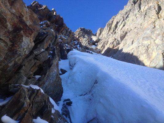 Aufstieg durch ein steiles, eingeschneites Couloir.