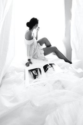 Dirk Brzoska Fotografie 2016 in schwarzweiss - asiatische Frau mit dunklen langen Haaren sitzt im Brautkleid neben ihr ein Bildband und schaut aus dem Fenster