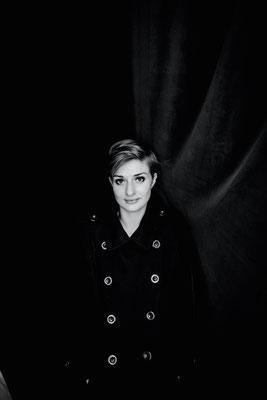 Dirk Brzoska Fotografie 2016 in schwarzweiss - junge Frau in einem langen schwarzen Mantel mit grossen Knöpfen blickt vor einem dunklen Vorhang in die Kamera