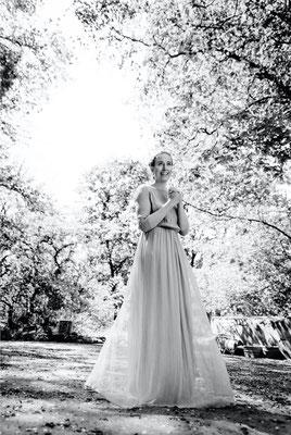 Dirk Brzoska Fotografie 2016 in schwarzweiss - Frau mit blonden Haaren stehend mit langem Kleid unter Bäumen mit Blüten