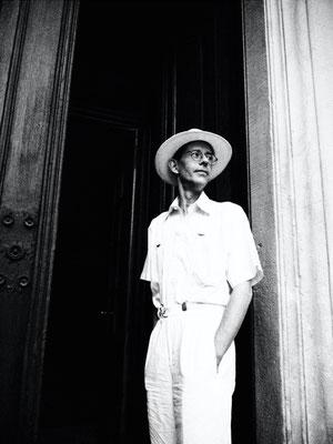 Dirk Brzoska Fotografie 2016 in schwarzweiss - Mann steht ganz in weiss mit Hemd Hose und Hut in der Tür einer alten Villa