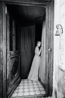 Dirk Brzoska Fotografie 2016 in schwarzweiss - Frau in langem Kleid blickt zurück durch eine geöffnete alte Tür mit Glocke