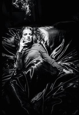 Dirk Brzoska Fotografie 2016 in schwarzweiss - Frau liegt mit Zigarette auf schwarzen Samt neben ihr eine Olympus pen und erinnert mich an Romy Schneider