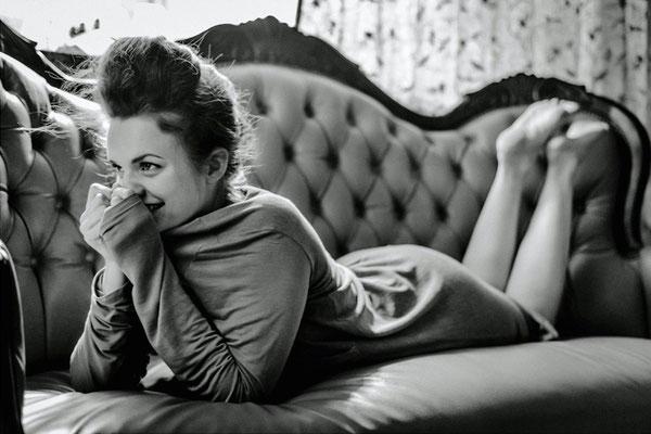 Dirk Brzoska Fotografie 2016 in schwarzweiss - junge Frau mit dunklen Haaren liegt in langem Kleid auf dem alten Sofa einer Villa und lächelt