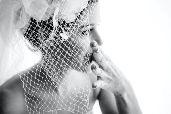 Dirk Brzoska Fotografie 2016 in schwarzweiss - Braut in weissem Kleid mit Schleier und lackierten Fingernägeln im Gegenlicht vor einem Fenster