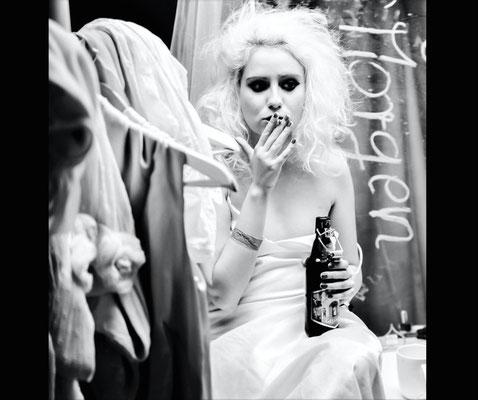 Dirk Brzoska Fotografie 2016 in schwarzweiss - junge Frau mit blonden Haaren Zigarette und Bierflasche sitzend im weissen Kleid vor einem Spiegel