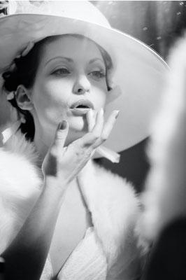 Dirk Brzoska Fotografie 2016 in schwarzweiss - Frau im Brautkleid weissem Hut und Stola schminkt sich die Lippen vor einem Spiegel