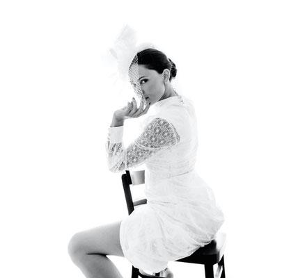 Dirk Brzoska Fotografie 2016 in schwarzweiss - Braut mit dunklen Haaren sitzt mit kurzem Kleid und Schleier auf Holzstuhl und blickt im Gegenlicht über ihre Schulter