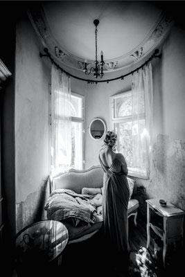 Dirk Brzoska Fotografie 2016 in schwarzweiss - Frau in langem Kleid mit freiem Rücken schaut aus dem Fenster