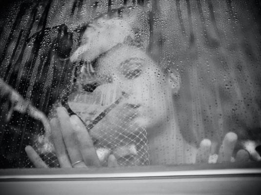 Dirk Brzoska Fotografie 2016 in schwarzweiss - Braut mit dunklen langen Haaren und Schleier fascinator blickt durch die verregnete Autoscheibe eines Mercedes auf die sie ein Herz malt