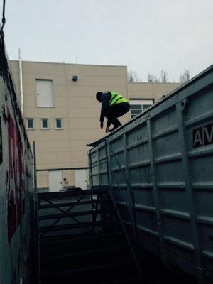 Versteckperson am Container