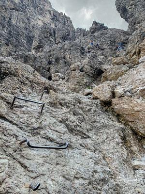 Nach dem anstrengenden Aufstieg über das steile Geröll erreicht man den Felsriegel am oberen Ende des Tales mit den ersten Drahtseilen und Leitern.