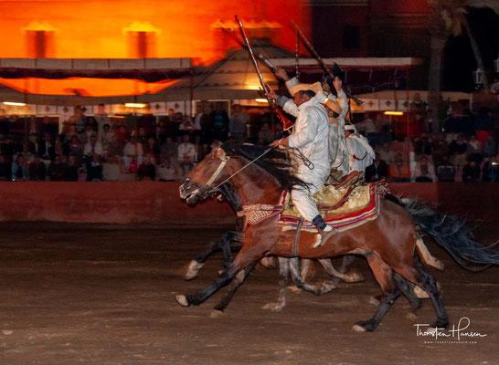 Die Fantasia wird von einer Gruppe von Reitern in traditionellen Gewändern auf in der Regel Berber-Rassepferden durchgeführt, die in einer geraden Linie nebeneinander mit gleich hoher Geschwindigkeit galoppieren
