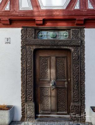 """Das schlichte Erdgeschoß wird durch eine kunstvoll geschnitzte Holztür, die die Inschrift """"Soli Deo Gloria"""" und die Jahreszahl 1697 trägt"""