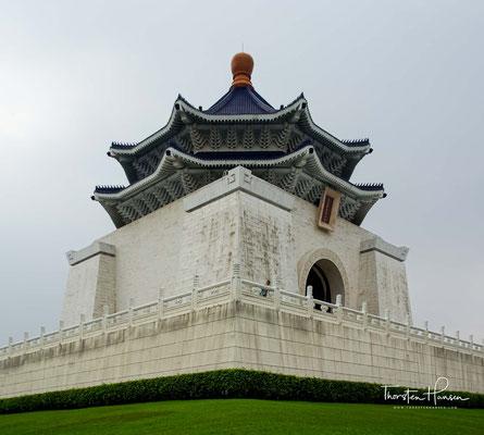 """Der weiß-blaue Stil des Gebäudes mit den roten Blumenbeeten steht für die Farben der Flagge der Republik China. Die oktogonale Form symbolisiert die Zahl 8, die traditionell in Asien für """"Fülle und Geschick"""" steht."""