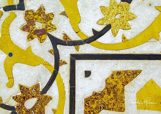 Die Front der oberen, nach außen leicht abfallenden Plattform ist mit einem geometrischen Muster aus roten Sandstein- und weißen Marmorintarsien geschmückt.