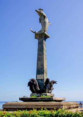 """Das Dorf Kalibukbuk ist Lovinas eigentliches Zentrum. Weithin sichtbar ist die Delfin-Statue """"Patung Lumba Lumba"""" am zentralen Platz"""