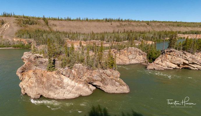 """Die Tutchone nennen die Stromschnellen Tthi-chò nädezhé, was so viel bedeutet wie """"Felsen, die im Wasser stehen""""."""